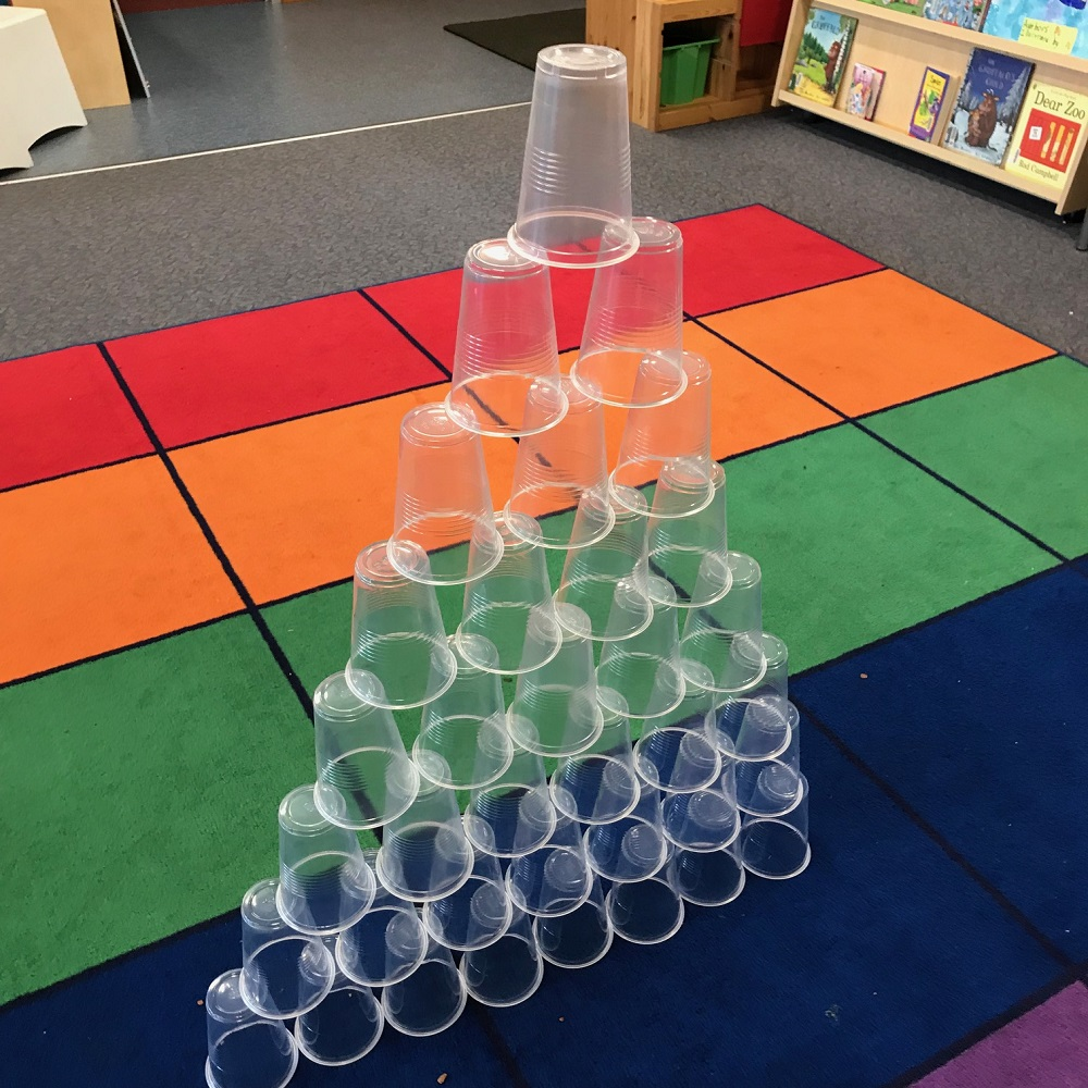 Plastic cups grouped together to form a pyramid tower