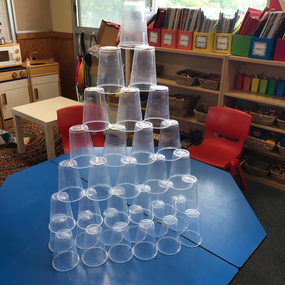 Plastic cups grouped together to form a pyramid tower on classroom table