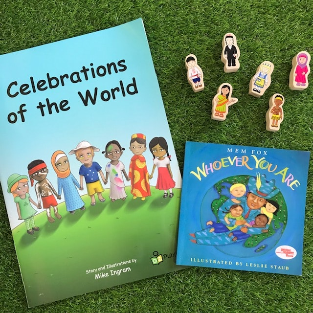 Celebrations of the world book with wooden figures on grass background