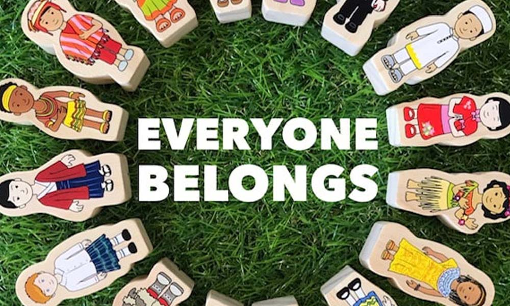 Everyone belongs title on grass background with wooden dolls