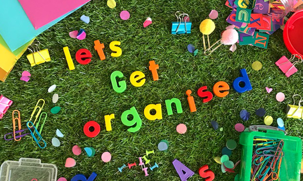 lets get orgainised magnetic lettering on grass background with teaching resources surrounding