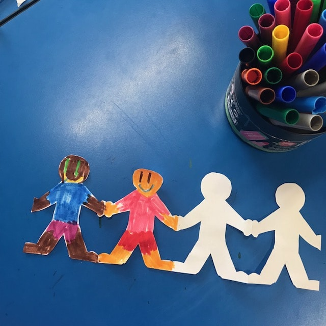 Paper chain dolls on classroom desk
