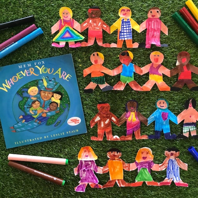 Paperchain dolls whoever you are book with coloured pens on grass background