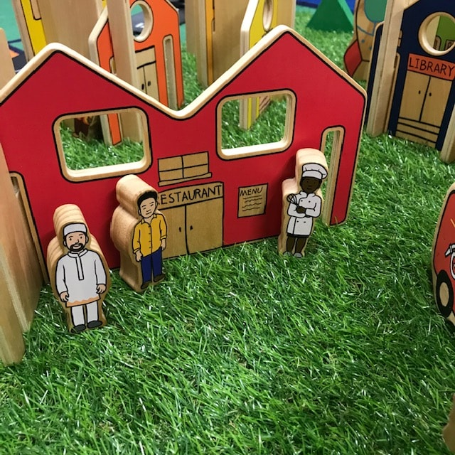 Wooden town and dolls on grass background