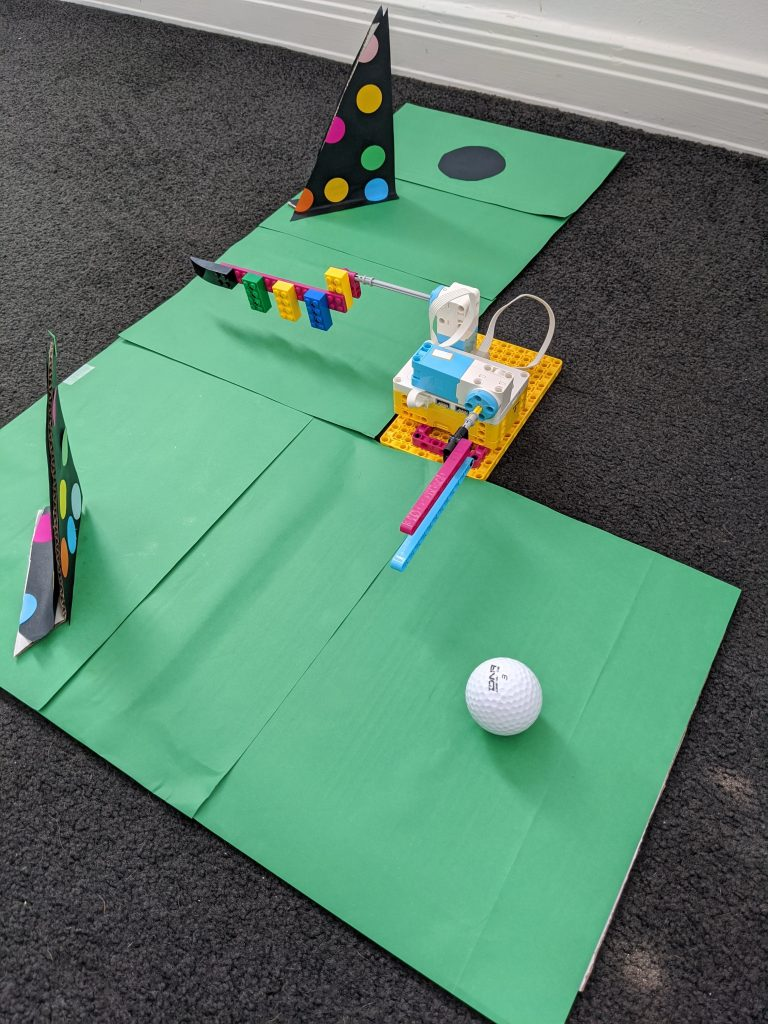 LEGO Spike Golf Course featuring Spike model grean card and golf ball on floor