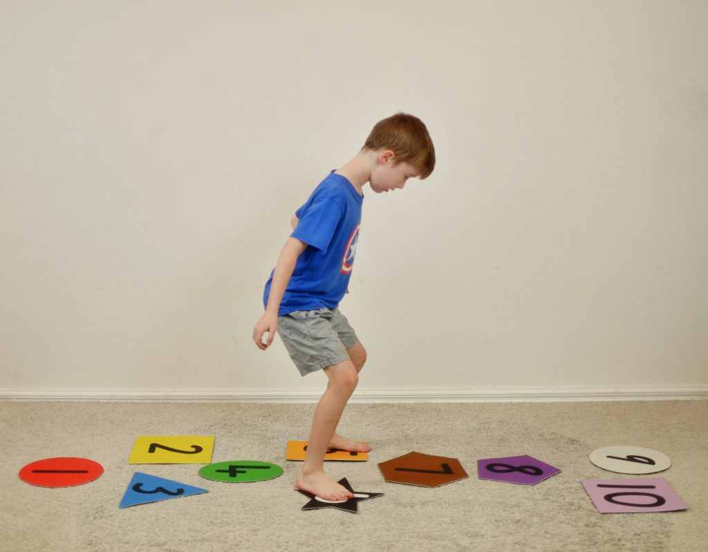Boy playing numbered hopscotch on carpet