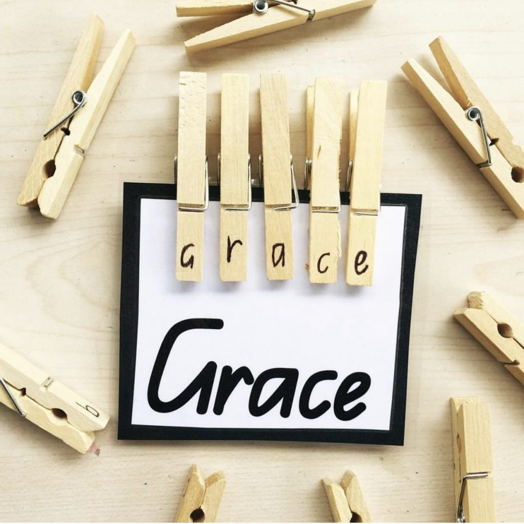 Peg name activity featuring pegs with letters on clipped to card with name spelt out