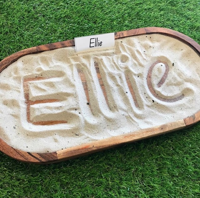 Sensory sand tray writing spelling out Ellie letters