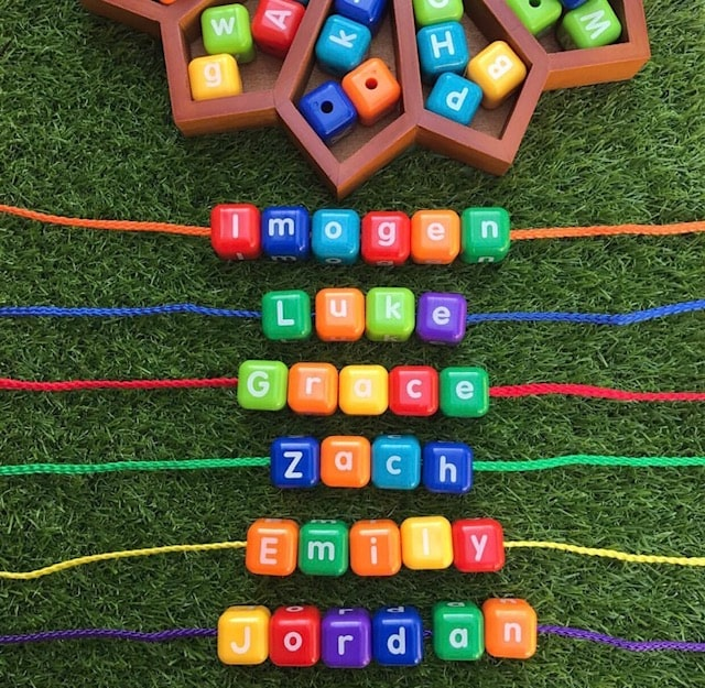 Threading letter beads spelling out childrens names on grass background