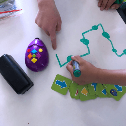Robot mouse coding cards child's hands drawing path using whiteboard marker
