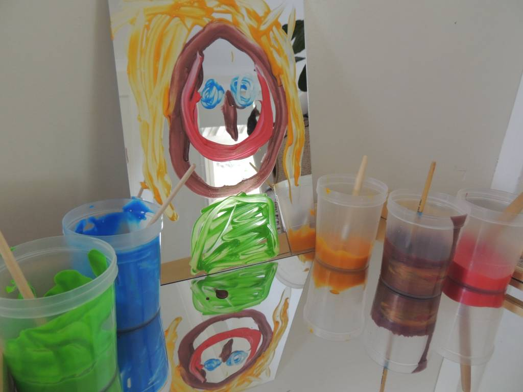 Mirrors and Reflections portrait activity featuring childs painting on a mirror and paint pots