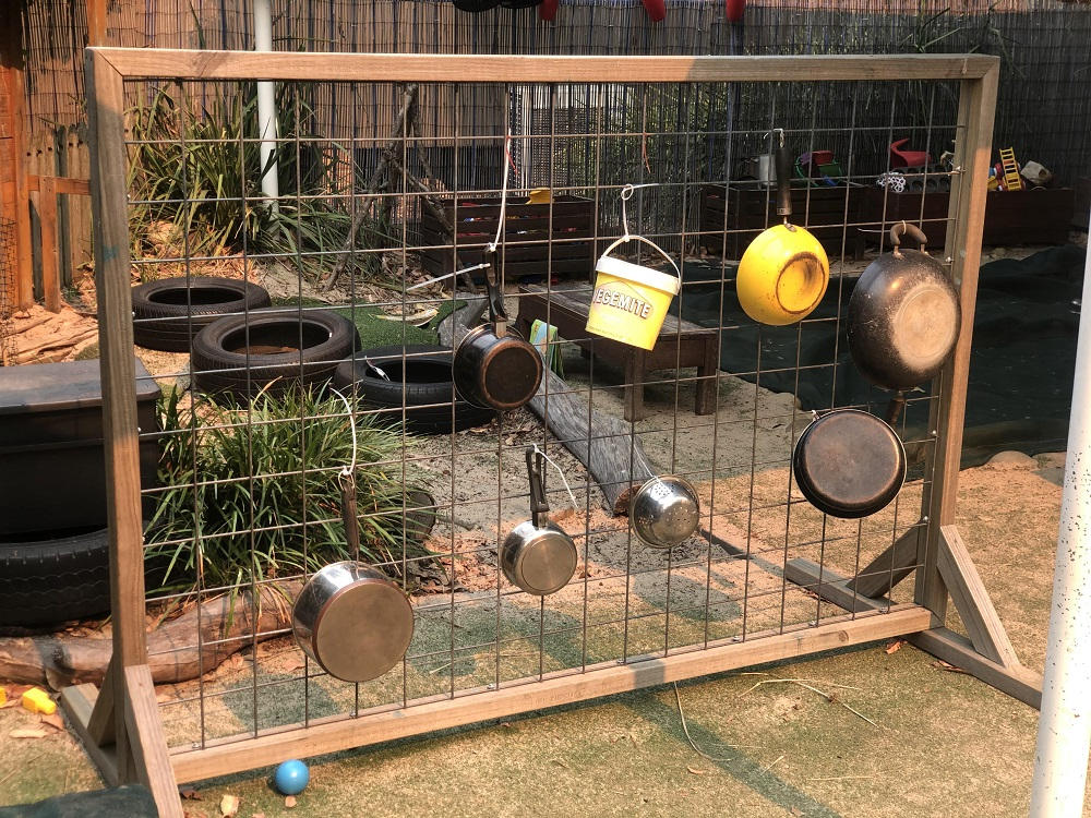 Pots and pans hanging from wooden frame in garden
