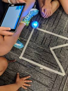 Sphero Angles and Shapes activity. Track on floor students holding tablet
