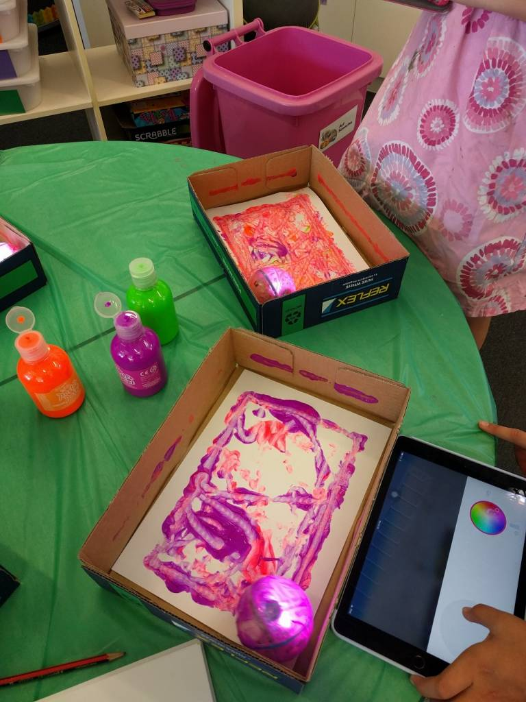Sphero Art activity. Sphero robots painting canvas inside boxes. Paints and tablet on table.