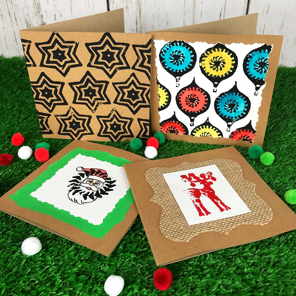 Christmas Craft Cards and pom poms on grass background
