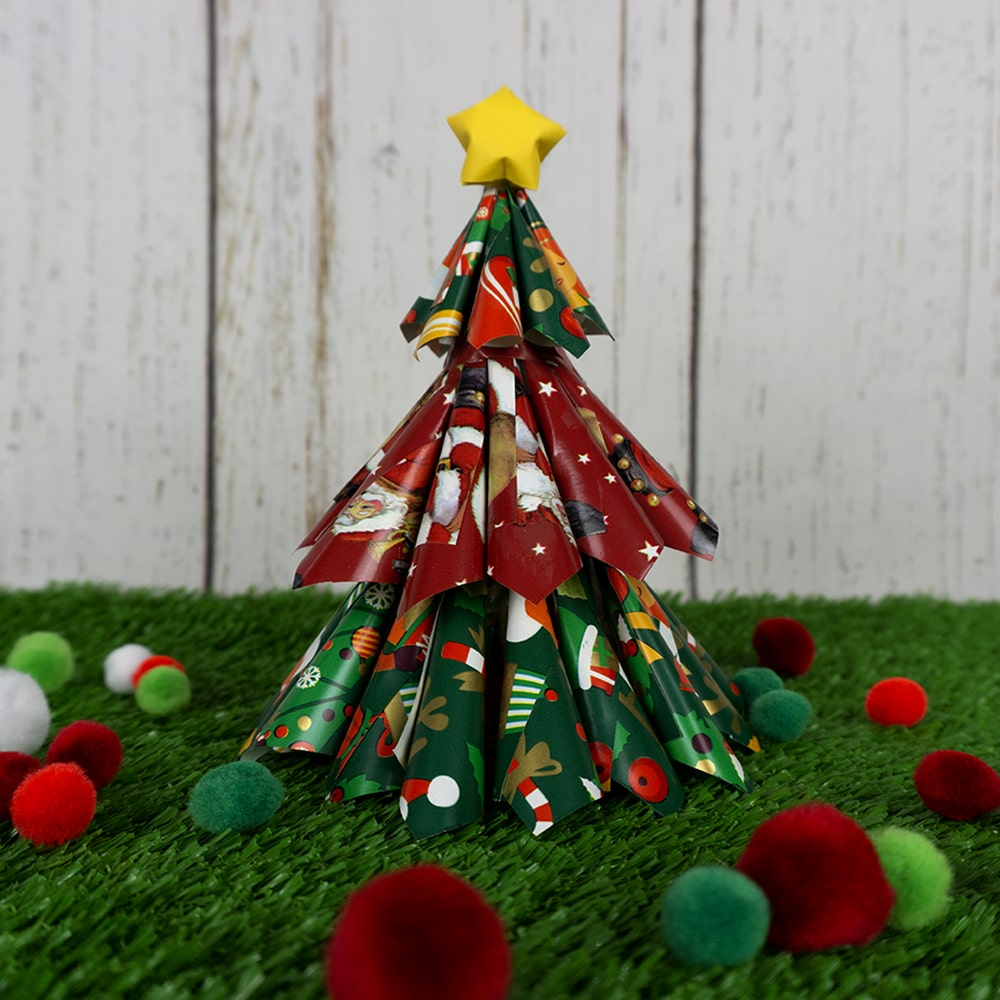 Christmas Tree and pom poms on grass background
