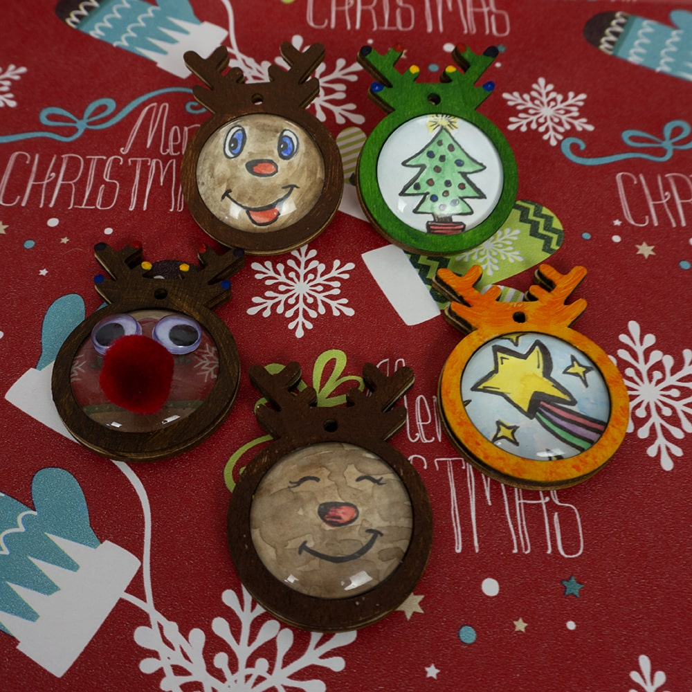Christmas craft ornaments sitting on Christmas paper